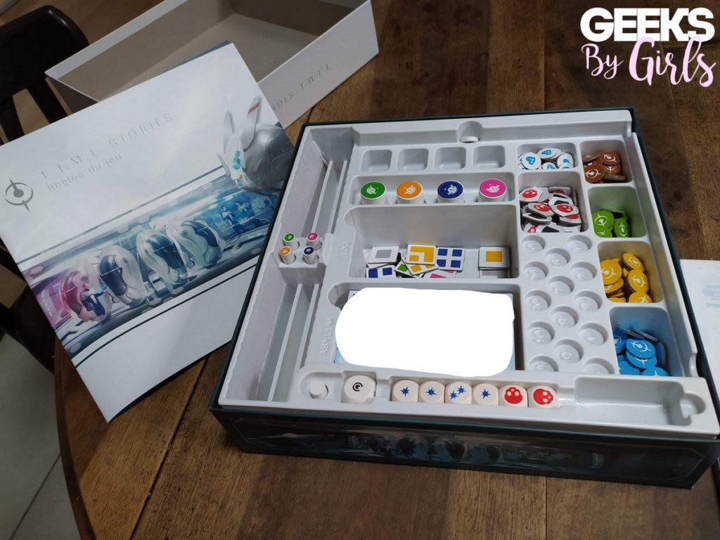 Boîte du jeu T.I.M.E Stories avec livret de règles, dés, jetons, et cartes Asylum.